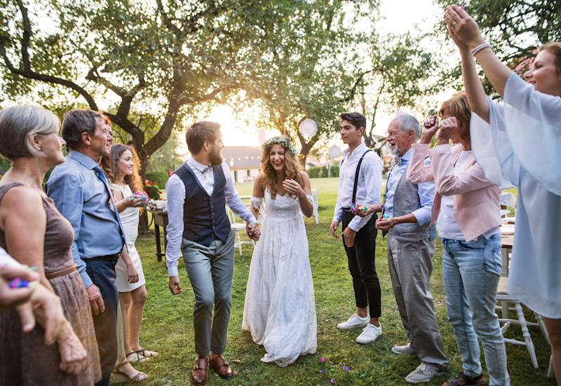 Bride, groom and their guests at the wedding reception outside in the backyard. Family celebration.