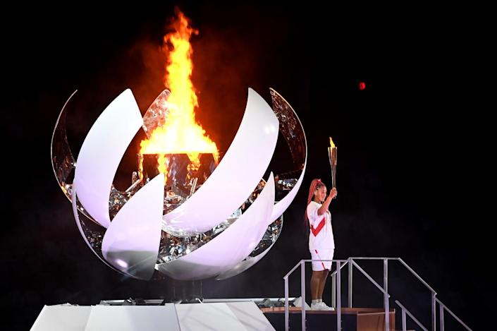 Naomi Osaka lights the Olympic torch during opening ceremony of the Tokyo Games.