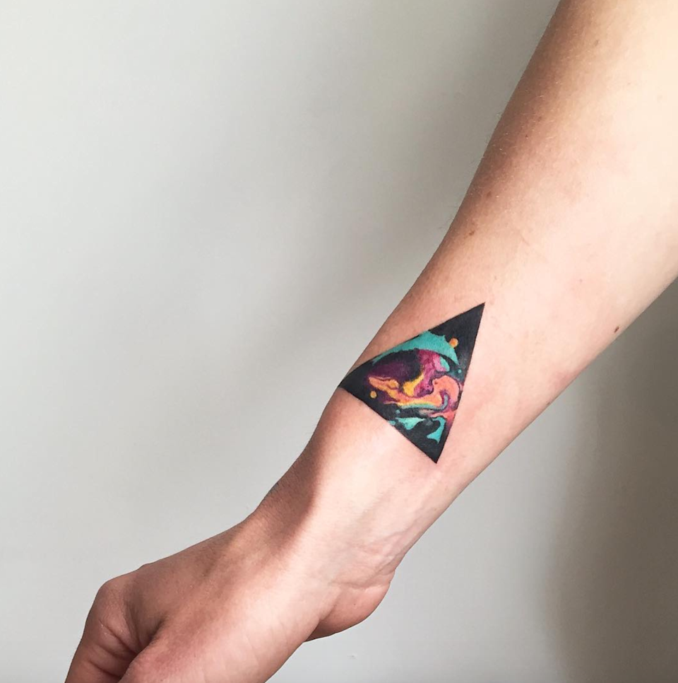 The triangle's black ink background makes every other color pop, from the turquoise to the yellow to the orange. A design of this size takes about an hour, according to Wachob.