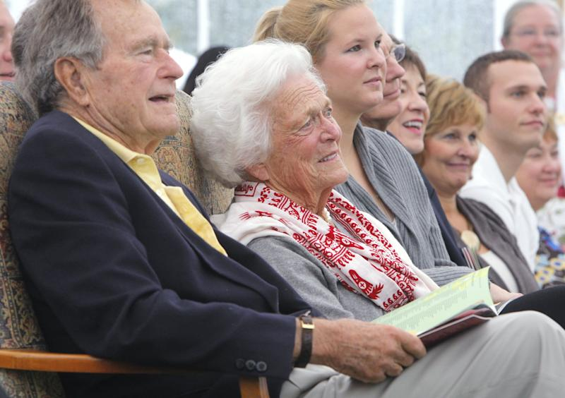 George H.W. Bush and his wife Barbara listen at a dedication ceremony for a garden honoring Barbara Bush at the town green in Kennebunkport, Maine, in 2011.