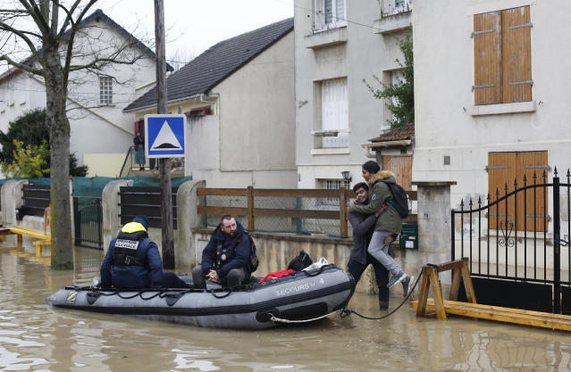 <p>Rescue workers evacuate residents in a flooded street of Villeneuve-Saint-Georges, outside Paris, where the Yerres river floods on Thursday, Jan.25, 2018. (Photo: Thibault Camus/AP) </p>
