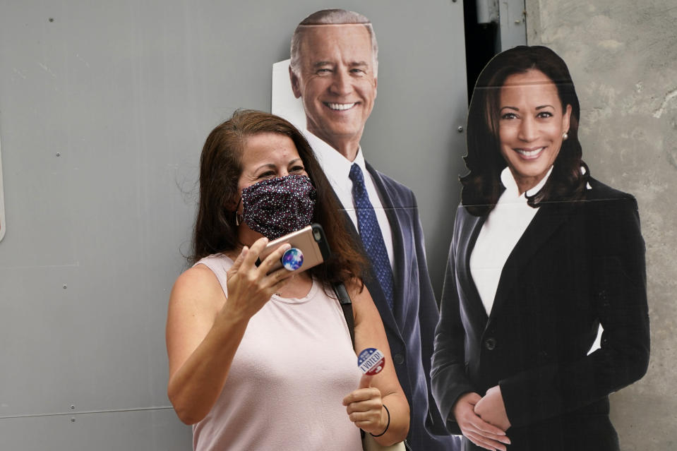 """Yaidi Clery, left, holds up an """"I Voted"""" sticker as she stands with a cutout of Democratic presidential candidate former Vice President Joe Biden, and candidate for Vice President Kamala Harris outside of an early voting site, Tuesday, Oct. 20, 2020, in Miami Beach, Fla. Florida begins in-person early voting in much of the state Monday. With its 29 electoral votes, Florida is crucial to both candidates in order to win the White House. (AP Photo/Lynne Sladky)"""