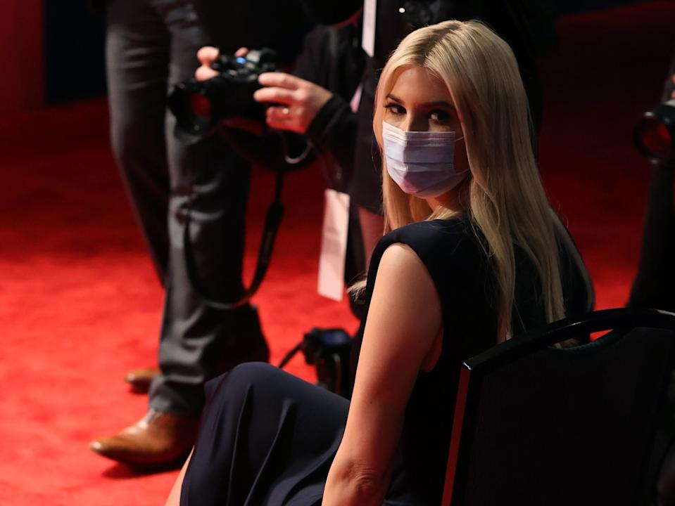Ivanka Trump wears a mask while sitting in a chair in the debate hall