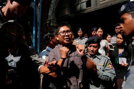 Detained Reuters journalist Wa Lone is escorted by police after a court hearing in Yangon, Myanmar March 7, 2018. REUTERS/Stringer