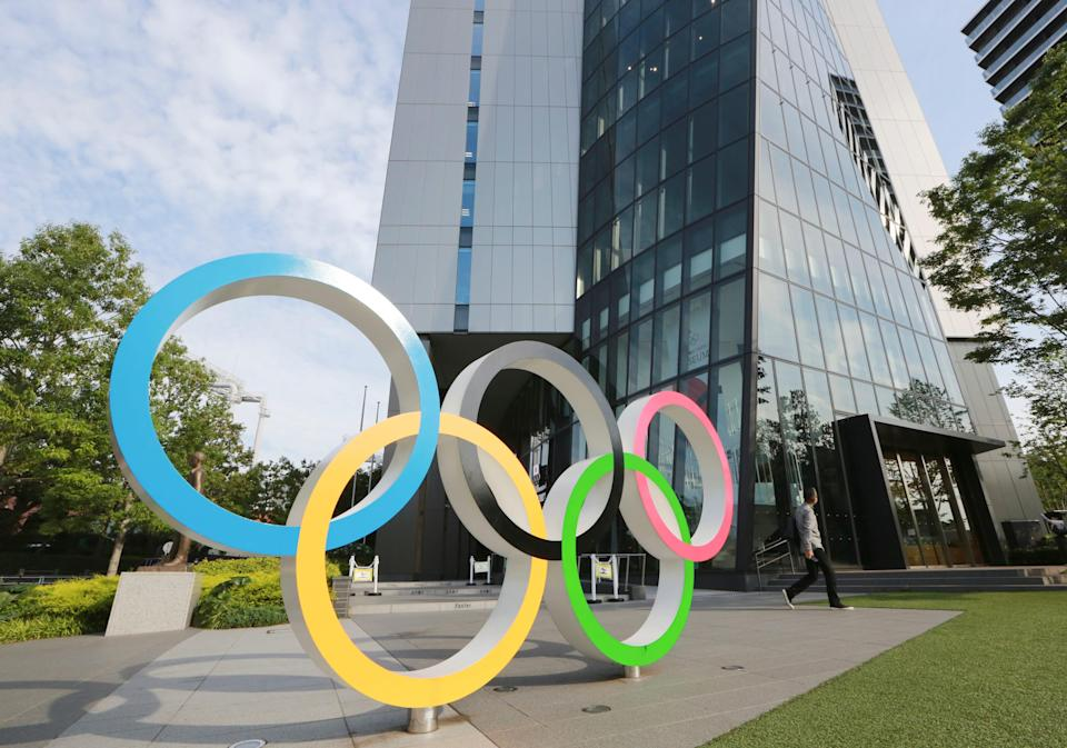 A man walks past the Olympic rings in Tokyo.
