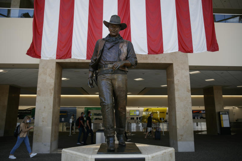 Travelers walk past a John Wayne statue at John Wayne Airport in Santa Ana, Calif, Monday, June 29, 2020. In the latest move to change place names in light of U.S. racial history, leaders of Orange County's Democratic Party are pushing to drop film legend Wayne's name, statue and other likenesses from the county's airport because of his racist and bigoted comments. (AP Photo/Jae C. Hong)