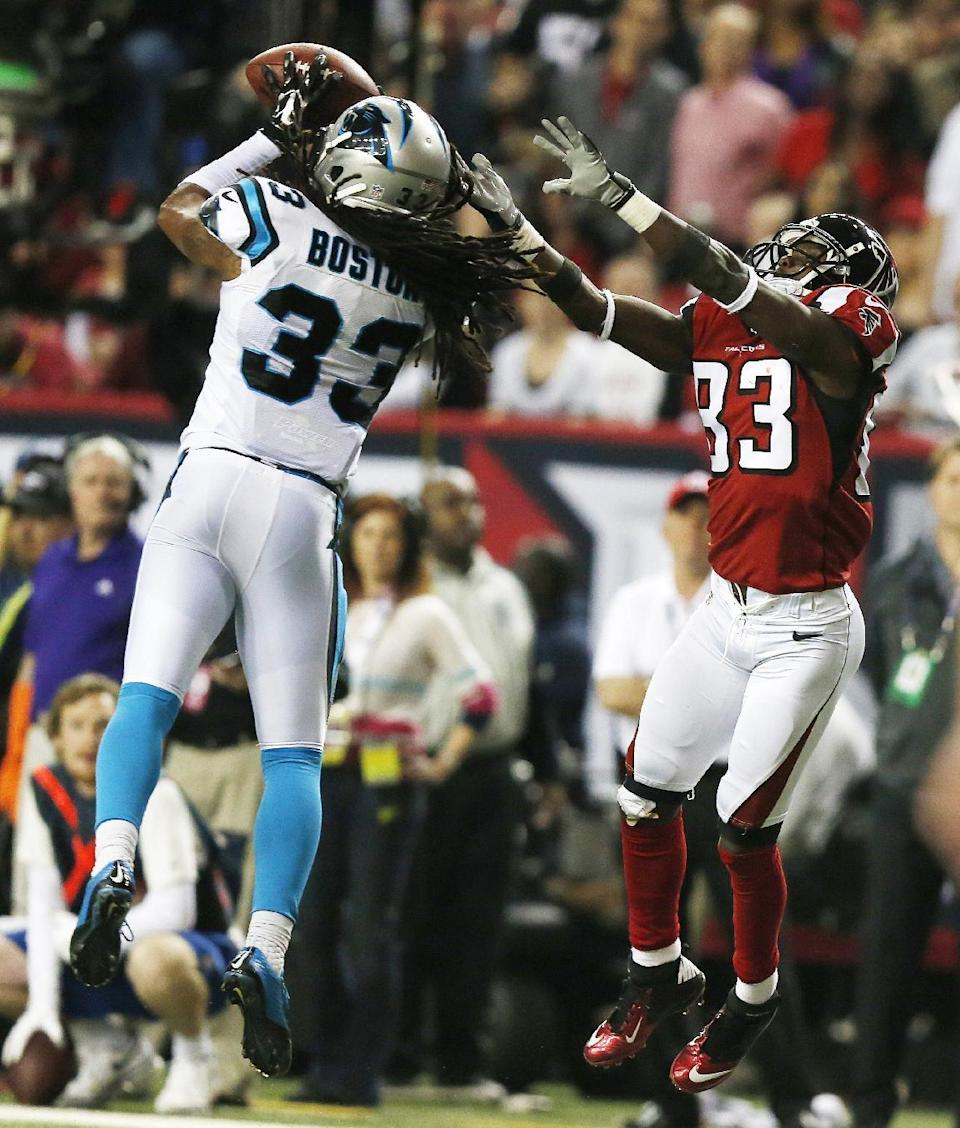 Carolina Panthers free safety Tre Boston (33) picks off a thrown ball intended for Atlanta Falcons wide receiver Harry Douglas (83) during the second half of an NFL football game, Sunday, Dec. 28, 2014, in Atlanta. Boston ran the ball back for a touchdown. (AP Photo/Brynn Anderson)