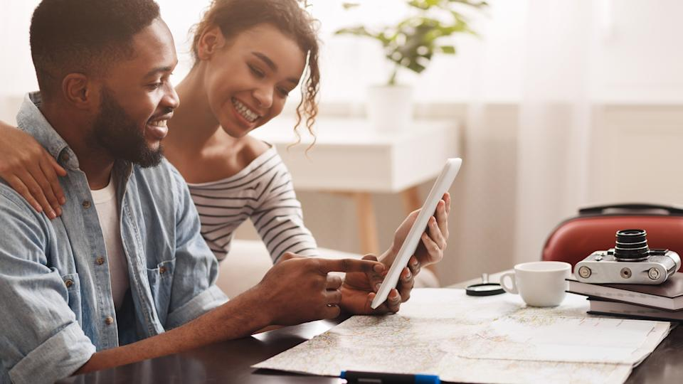 Planning vacation. Couple using tablet, searching places to visit