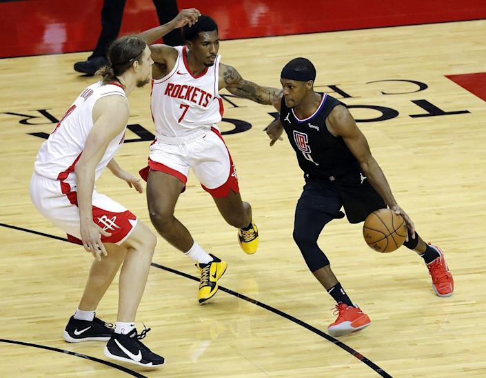 The Clippers' Rajon Rondo drives against the Rockets' Armoni Brooks (7) and Kelly Olynyk on May 14, 2021.