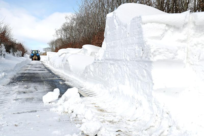 "A farmer in a tractor helps to clear the snow from a blocked road heading out of Simonsbath in Exmoor National park, as the icy conditions brought by the ""Mini Beast from the East"" are set to cling on for one more day before Britain will see the return of spring."