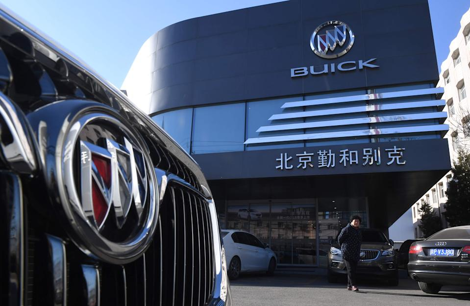 A woman stands outside a Buick showroom in Beijing on December 15, 2016.