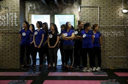 """Participants gather before the start of a workout session during TV program """"The Body Show"""" at a gym in Seoul, September 19, 2015. REUTERS/Kim Hong-Ji"""