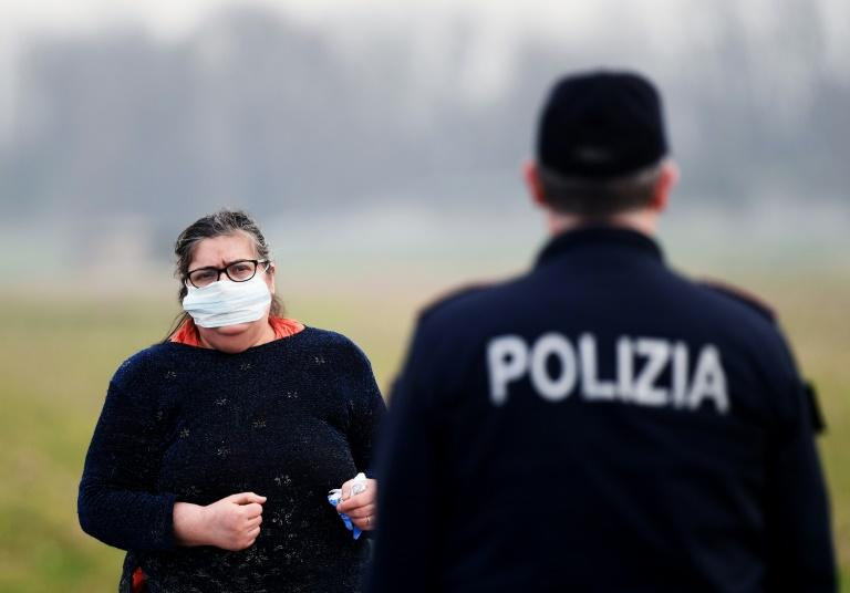 A resident wearing a respiratory mask (L) talks with a police officer at the entrance to the town of Casalpusterlengo, southeast of Milan, an area where most of Italy's new-coronavirus cases have emerged