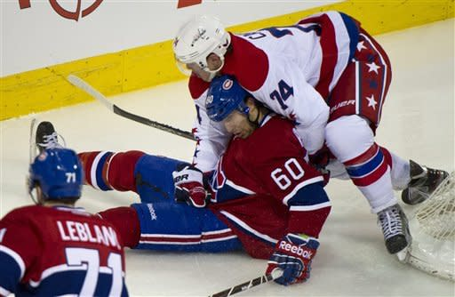 Montreal Canadiens' Erik Cole(60) is dumped by Washington Capitals' John Carlson during third period NHL hockey action, Saturday, Feb. 4, 2012 in Montreal. (AP Photo/The Canadian Press, Paul Chiasson)