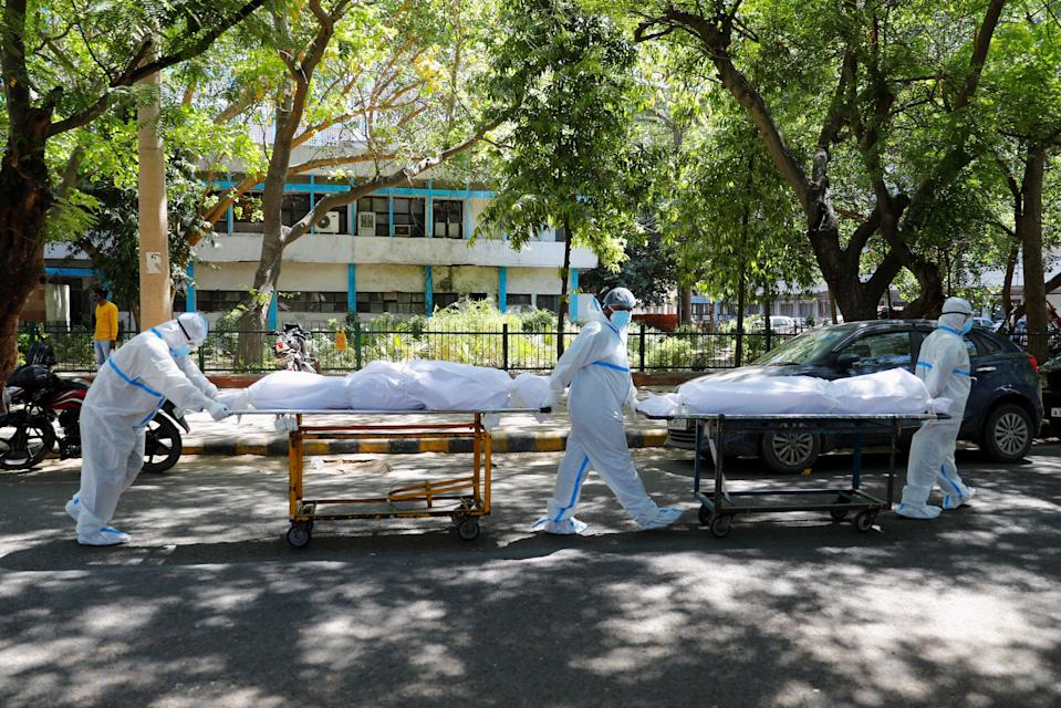 <p>Health workers carry bodies of people who were suffering from the coronavirus disease outside the Guru Teg Bahadur hospital, in New Delhi</p> (REUTERS)