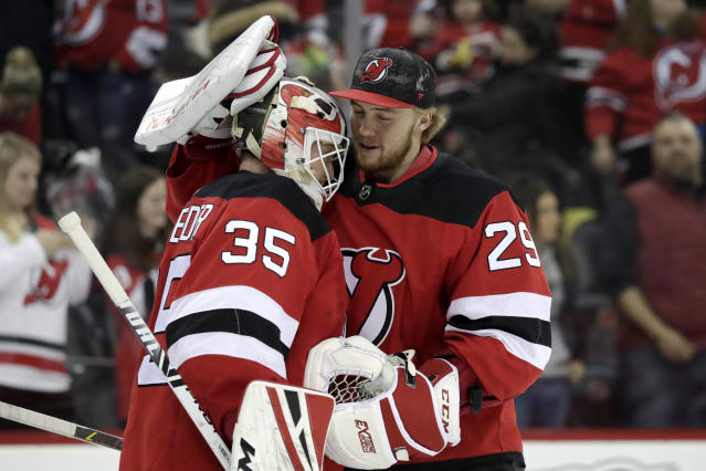 New Jersey Devils goaltender Cory Schneider (35) and goaltender MacKenzie Blackwood (29) celebrate after defeating the Buffalo Sabres 3-1 during an NHL hockey game, Monday, March 25, 2019, in Newark, N.J. (AP Photo/Julio Cortez)