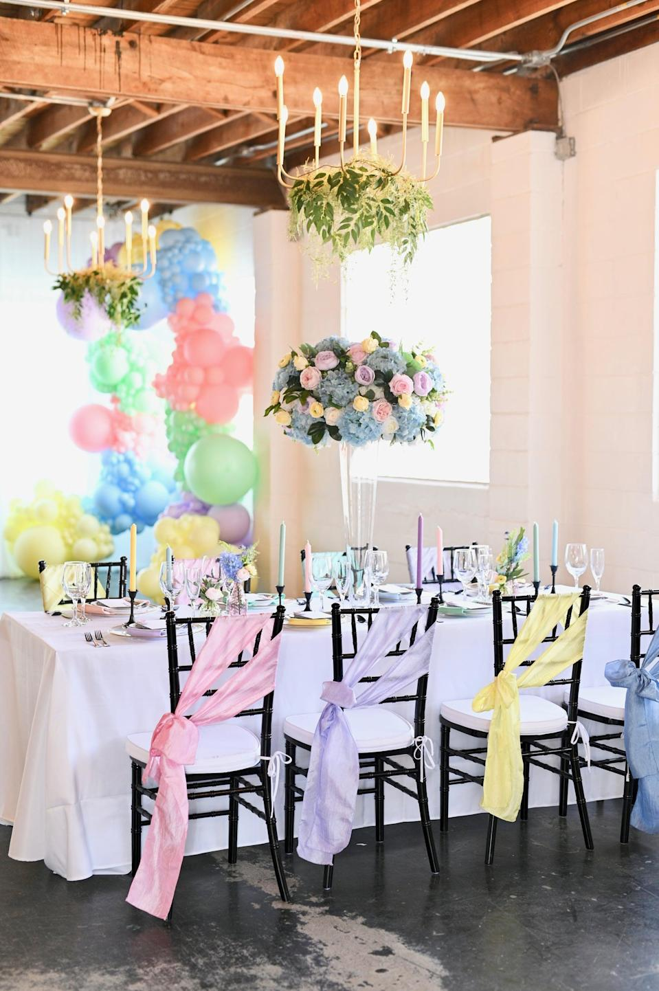 <p>If the future bride is all about bright colors, flower arrangements, and fun-filled photo ops, she would love a rainbow-themed bridal party. You'll just need balloons, flowers, and bright accessories (like the chair sashes pictured here) to make this theme shine bright.</p>