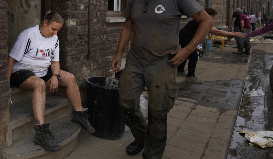 Resident Eric Mouque, center, walks by his wife Cindy Mouque as they take a rest after cleaning up their flood damaged home in the La Brouck neighborhood of Trooz, Belgium, Tuesday, July 27, 2021. The Mouque's are among hundreds of survivors in the small town of Trooz experiencing symptoms of post-traumatic stress disorder, depression and anxiety. (AP Photo/Virginia Mayo)