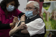 Okko Molenkamp, 94, is injected with a COVID-19 vaccine in Apeldoorn, Netherlands, Tuesday, Jan. 26, 2021. Dutch authorities began vaccinating the first of thousands of people aged over 90 years who still live at home. (AP Photo/Peter Dejong)