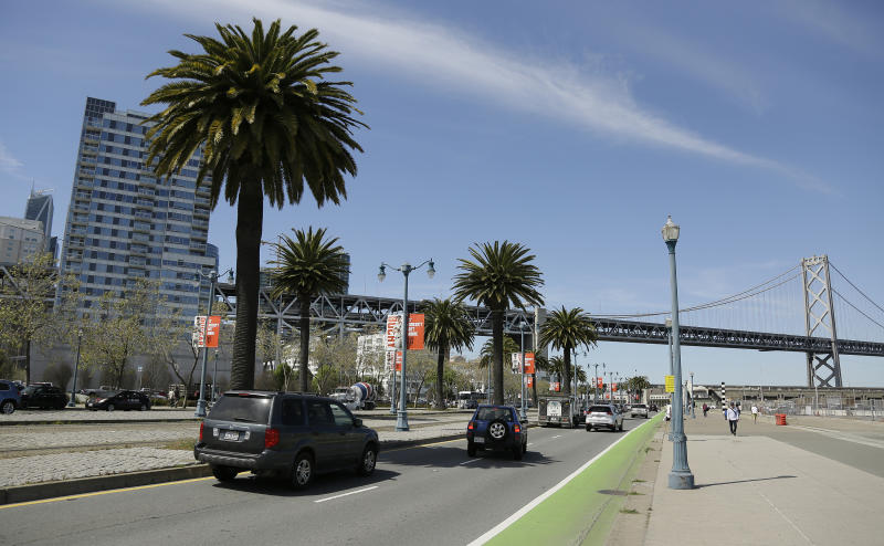 In this photo taken Thursday, April 18, 2019, cars make their way along the Embarcadero, with the San Francisco-Oakland Bay Bridge in the background, across the street from the proposed site of a homeless shelter in San Francisco. The city of San Francisco, which has too little housing and too many homeless people sleeping in the streets, is teeming with anxiety and vitriol these days. A large new homeless shelter is on track to go up along a scenic waterfront area dotted with high-rise luxury condos, prompting outrage from some residents. (AP Photo/Eric Risberg)