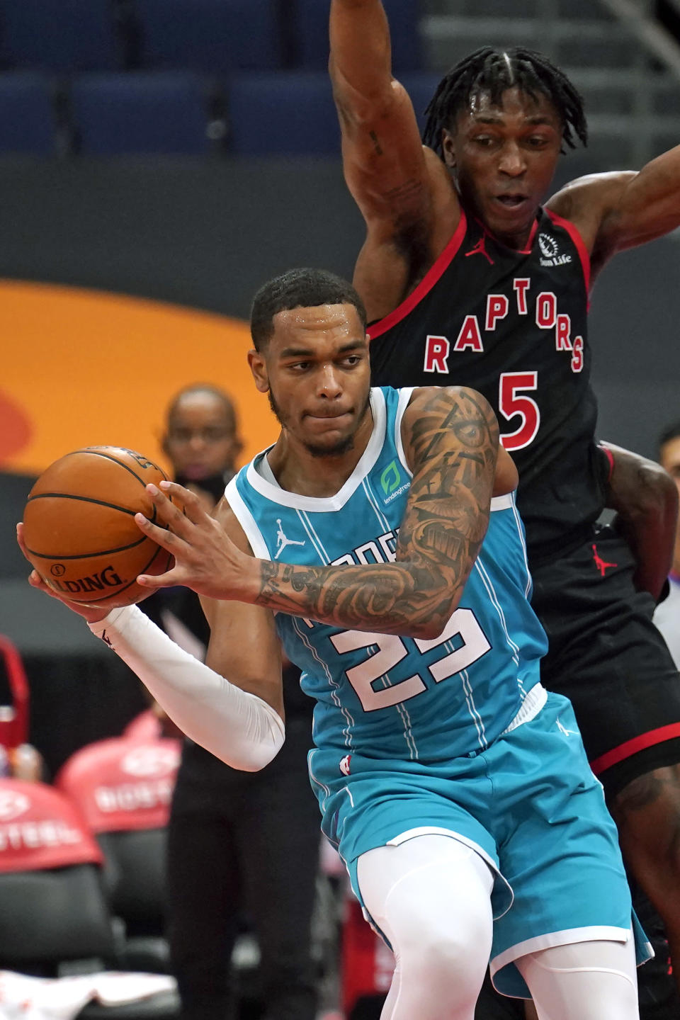 Charlotte Hornets forward P.J. Washington (25) makes a pass in front of Toronto Raptors forward Stanley Johnson (5) during the first half of an NBA basketball game Saturday, Jan. 16, 2021, in Tampa, Fla. (AP Photo/Chris O'Meara)