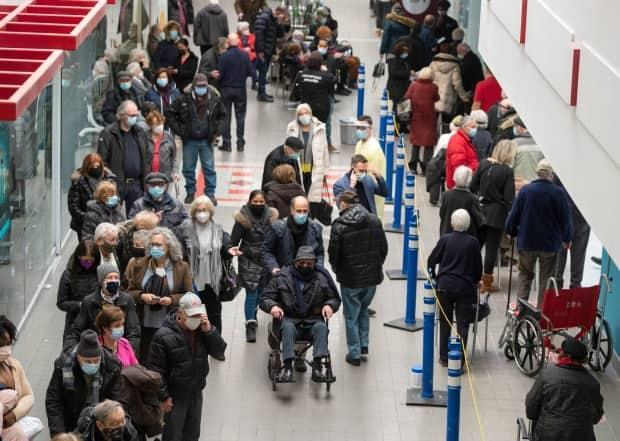 Crowds of people waited for their COVID-19 vaccinations at the Olympic Stadium in Montreal on Monday. It was one of about 15 sites that are now open to the public in the city.
