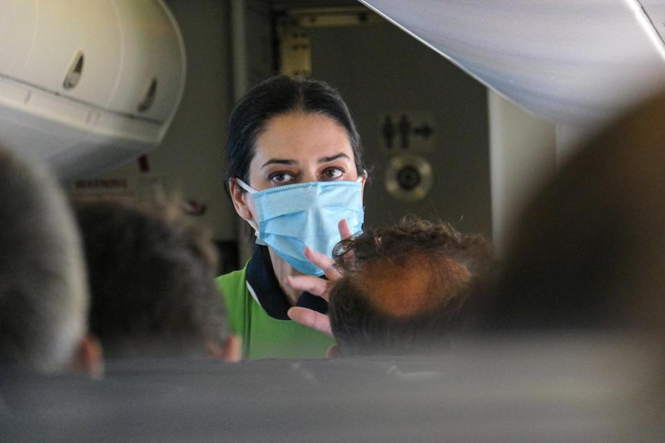 Close up portrait of a female air stewardess cabin crew during the flight. Flying in an Olympic Air De Havilland Canada DHC-8-400 Turboprop aircraft during the Covid-19 Coronavirus pandemic era with obligatory usage of face masks for the passengers. The flight crew, female air stewardess are wearing also safety equipment such as facemasks and gloves while the meals are changed and disinfecting napkin is provided.  The domestic flight route is from Athens ATH LGAV Airport, the Greek capital to the islands of Cyclades. Greeks and foreign pax travel to popular islands such as Mykonos or Santorini after the Greek Government lifted the traffic ban, lockdown quarantine measures for tourists, easing generally the measures to relaunch the tourism season, with more Covid tests at the airports and the entry points to Greece. Although there are still some countries whose citizens are banned due to the increased numbers of Coronavirus cases. July 14, 2020 (Photo by Nicolas Economou/NurPhoto via Getty Images)