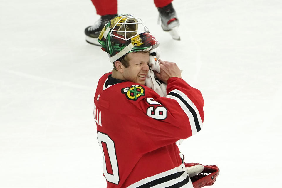 Chicago Blackhawks goaltender Collin Delia wipes his face during a break in the action in the second period of an NHL hockey game against the Dallas Stars Monday, May 10, 2021, in Chicago. (AP Photo/Charles Rex Arbogast)