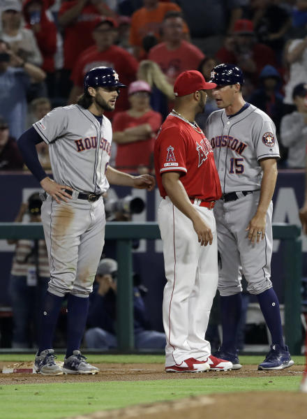 Los Angeles Angels first baseman Albert Pujols, center, argues with Houston Astros first base coach Don Kelly (15) after Astros' Jake Marisnick, left, was hit by a pitch during the sixth inning of a baseball game Tuesday, July 16, 2019, in Anaheim, Calif. (AP Photo/Marcio Jose Sanchez)