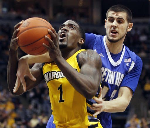 Seton Hall's Aaron Geramipoor, right, fouls Marquette's Darius Johnson-Odom (1) during the first half of an NCAA college basketball game, Tuesday, Jan. 31, 2012, in Milwaukee. (AP Photo/Jeffrey Phelps)