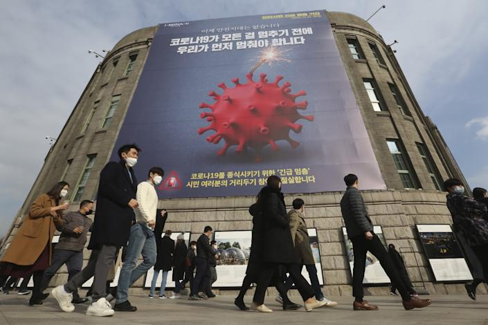 People wearing face masks walk past a coronavirus safety banner ad advising an enhanced social distancing campaign in Seoul.