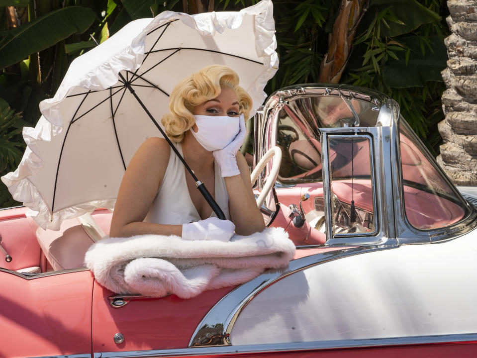 """FILE - In this Friday, April 16, 2021, file photo, an actress playing a Marilyn Monroe character wears a face mask as she poses for pictures at Universal Studios Hollywood theme park in Los Angeles. The park officially reopens to the public at 25% capacity with COVID-19 protocols in place. California Gov. Gavin Newsom appeared disinclined Friday, June 4, 2021, to insert himself into the regulatory process for workplaces after a state safety board upset business groups by approving new rules that require all workers to wear masks unless everyone around them is vaccinated against the coronavirus, The revised rules, approved after a long and sometimes contentious meeting Thursday, eliminate social distancing requirements but run counter to Newsom's plan to """"fully"""" reopen California in less than two weeks and allow vaccinated people to skip face coverings in nearly all situations. (AP Photo/Damian Dovarganes, File)"""