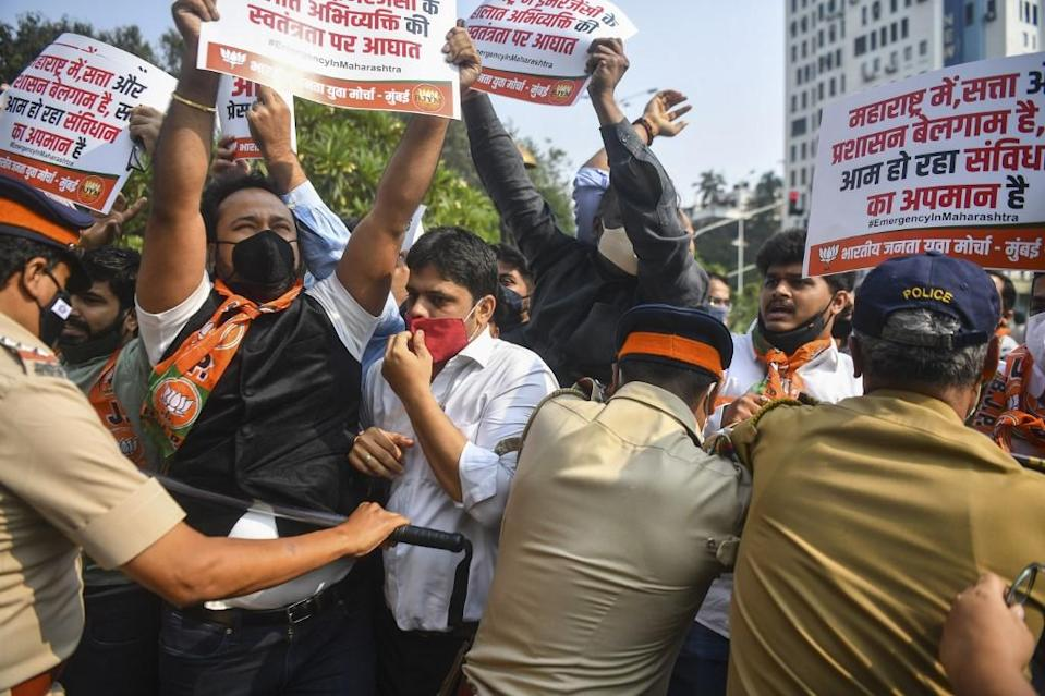 Activists and supporters of Bharatiya Janata Party (BJP) hold placards as they scuffle with police while protesting against the arrest of Indian television journalist Arnab Goswami, in Mumbai on November 4, 2020.