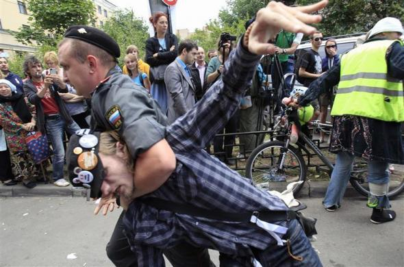 """Police detain a supporter of the female punk band """"Pussy Riot"""" members for violation of law and order outside a court building in Moscow, August 17, 2012."""