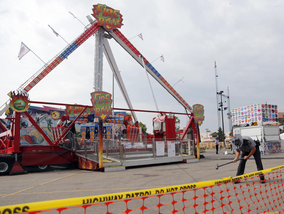 FILE- In this July 27, 2017 file photo, an Ohio State Highway Patrol trooper removes a ground spike in front of the Fire Ball ride at the Ohio State Fair, in Columbus, Ohio. Ohio has beefed up its amusement ride inspections four years after the ride broke apart at the 2017 Ohio State Fair and killed a high school student and injured several others. But some ride operators and festival organizers say the state's inspectors are overreaching and shutting down rides over issues that aren't safety-related. (AP Photo/Jay LaPrete, File)