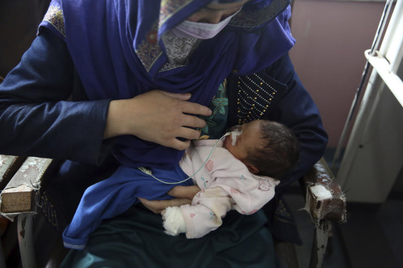 A mother holds her two-day-old baby at the Ataturk Children's Hospital, a day after they were rescued following a deadly attack on another maternity hospital, in Kabul, Afghanistan, Wednesday, May 13, 2020. Militants stormed the Barchi National Maternity Hospital in the western part of Kabul on Tuesday, setting off an hours-long shootout with the police and killing tens of people, including two newborn babies, their mothers and an unspecified number of nurses, Afghan officials said. (AP Photo/Rahmat Gul)