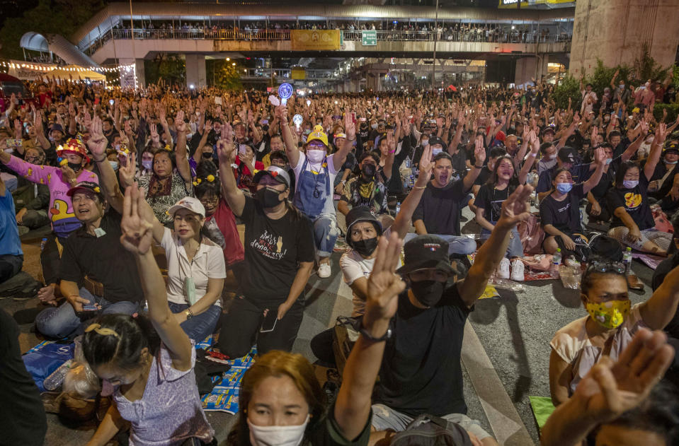 Anti-government protesters flash a three finger protest gesture during a rally Wednesday, Dec. 2, 2020, in Bangkok, Thailand. Thailand's highest court Wednesday acquitted Prime Minister Prayuth Chan-ocha of breaching ethics clauses in the country's constitution, allowing him to stay in his job.( AP Photo/Gemunu Amarasinghe)