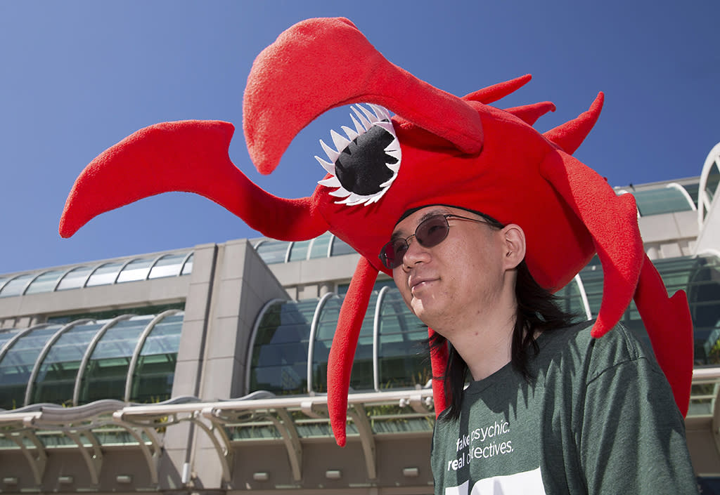 "John Masuzumi wearing a ""Hellbug"" hat from the science fiction TV series and video game ""Defiance"" stands in front of the San Diego Convention Center a day before the start of the 2013 Comic-Con in San Diego, California July 17, 2013. REUTERS/Fred Greaves (UNITED STATES - Tags: ENTERTAINMENT SOCIETY)"