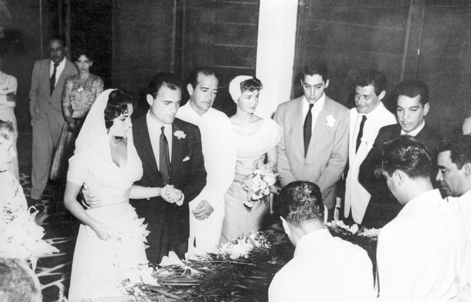 Elizabeth Taylor and film producer Mike Todd's 1957 wedding. Debbie Reynolds, matron of honor, is holding the flowers in the center of the photo, while Eddie Fisher is to her right in the white suit. (Photo: Getty Images)