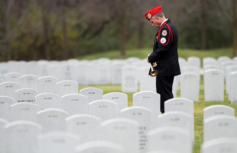 FILE - In this Saturday, Nov. 14, 2009, file photo, a military bugler waits for the funeral procession of Pfc. Michael Pearson to arrive at the Abraham Lincoln National Cemetery in Elwood, Ill. Pearson was one of 13 killed during the Fort Hood shootings. Maj. Nidal Hasan will stand trial, in a court-martial that starts Tuesday, for the shooting rampage at Fort Hood, Texas, that left 13 people dead and more than 30 people wounded on Nov. 5, 2009(AP Photo/John Smierciak, File)