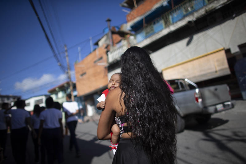 In this July 25, 2019 photo, 15-year-old Nicol Ramirez carries her baby girl to a lab where she will pay to get a pregnancy test, a prerequisite for a hormonal implant to prevent future pregnancies, of which there is a very limited number, in the Caucaguita neighborhood on the outskirts of Caracas, Venezuela. With condoms and birth control pills either impossible to find or too expensive, Ramírez found out she was pregnant at 14 with her boyfriend, who responded coldly to her pregnancy and hasn't heard from him since. (AP Photo/Ariana Cubillos)