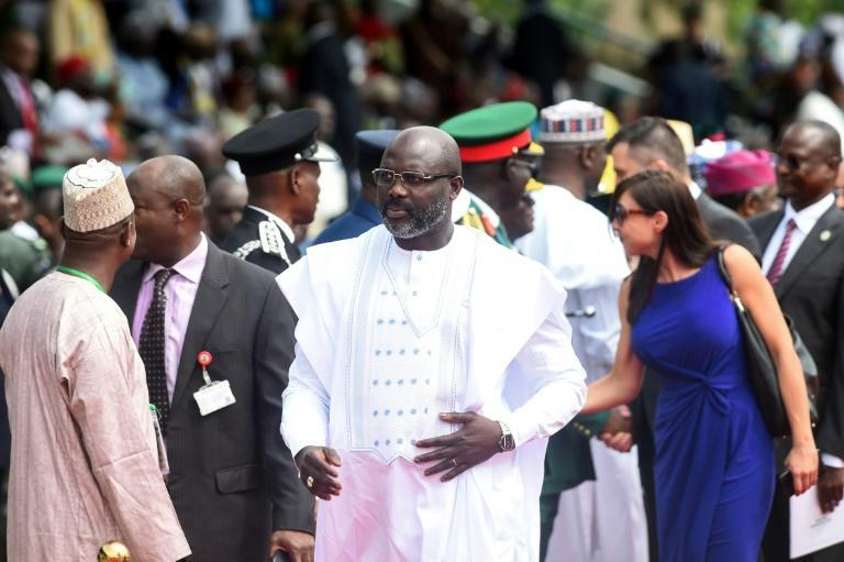 Thousands of Liberian civil servants have not been paid for months, intensifying worries about potential economic mismanagement under President George Weah (C) -- seen here in Abuja, Nigeria, on June 12, 2019 (AFP Photo/PIUS UTOMI EKPEI)