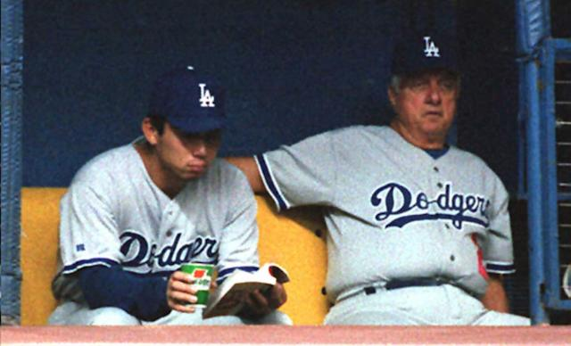 """Dodgers pitcher Hideo Nomo reads a book as manager Tom Lasorda watches the game against the Expos on Aug. 23, 1995, in Montreal. <span class=""""copyright"""">(Andre Pichette / AFP via Getty Images)</span>"""