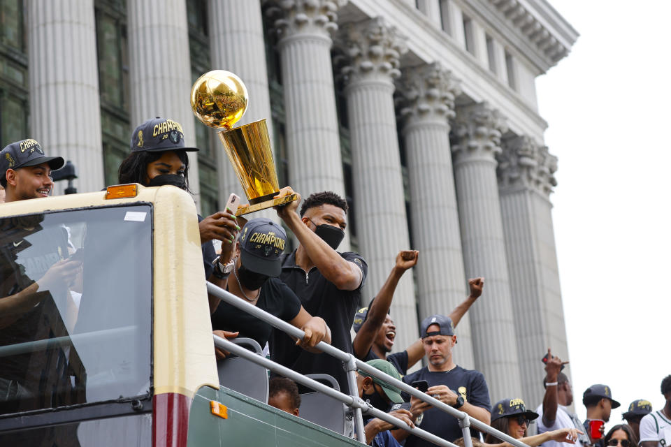 Milwaukee Bucks' Giannis Antetokounmpo holds up the NBA Championship trophy during a parade and celebration for the basketball team Thursday, July 22, 2021, in Milwaukee. (AP Photo/Jeffrey Phelps)