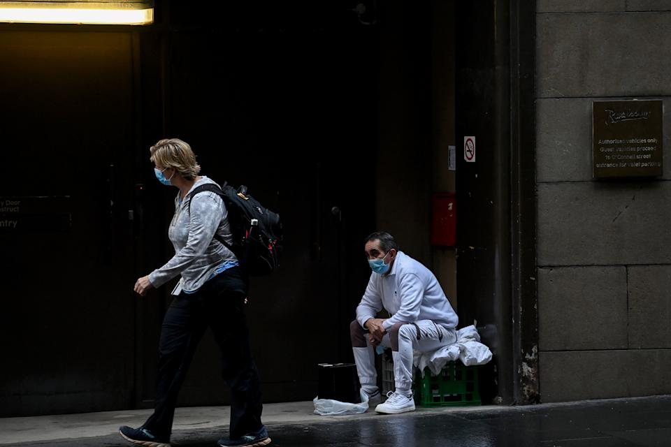 Two people wearing face masks on a Sydney street as Covid-19 continues to run rampant in the city.