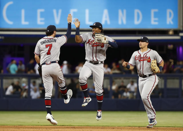 Atlanta Braves shortstop Dansby Swanson (7), left fielder Ronald Acuna Jr., center, and third baseman Austin Riley celebrate after the Braves defeated the Miami Marlins 7-1 in a baseball game Friday, June 7, 2019, in Miami. (AP Photo/Wilfredo Lee)