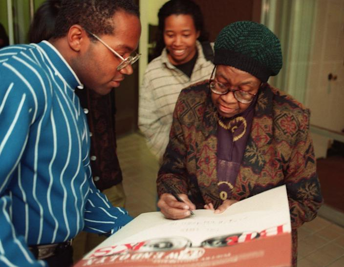 A Black woman wearng glasses and a green hat signs a poster.