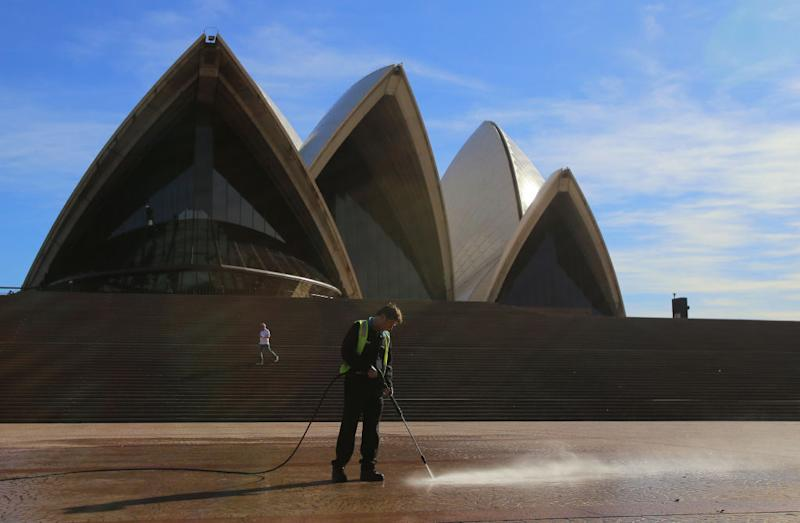 A worker uses a water-blaster to clean the ground in front of the Sydney Opera House, following an outbreak of coronavirus in Sydney.