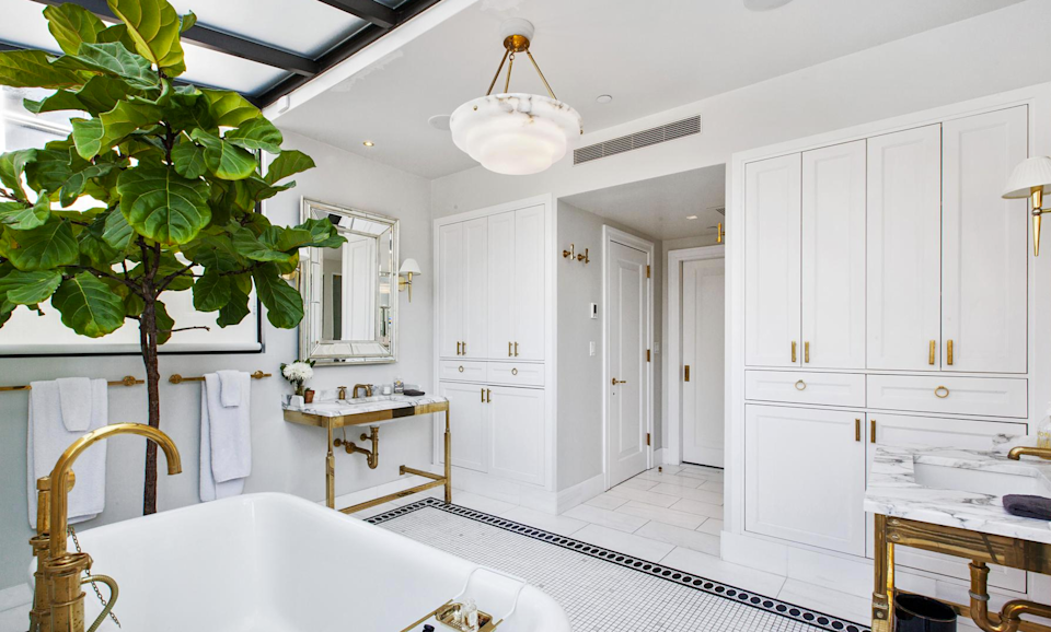 <p>The bathroom also boasts white lacquered custom cabinets and hand-laid tile flooring. (Douglas Elliman) </p>
