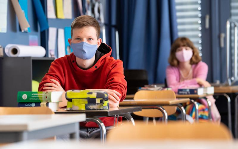 27 April 2020, Bavaria, Unterhaching: Pupils of a 12th grade of the Lise-Meitner-Gymnasium take part in the lessons and wear mouthguards. After a six-week break, some graduating classes in Bavaria are back in school with attendance lessons. Photo: Sven Hoppe/dpa (Photo by Sven Hoppe/picture alliance via Getty Images)